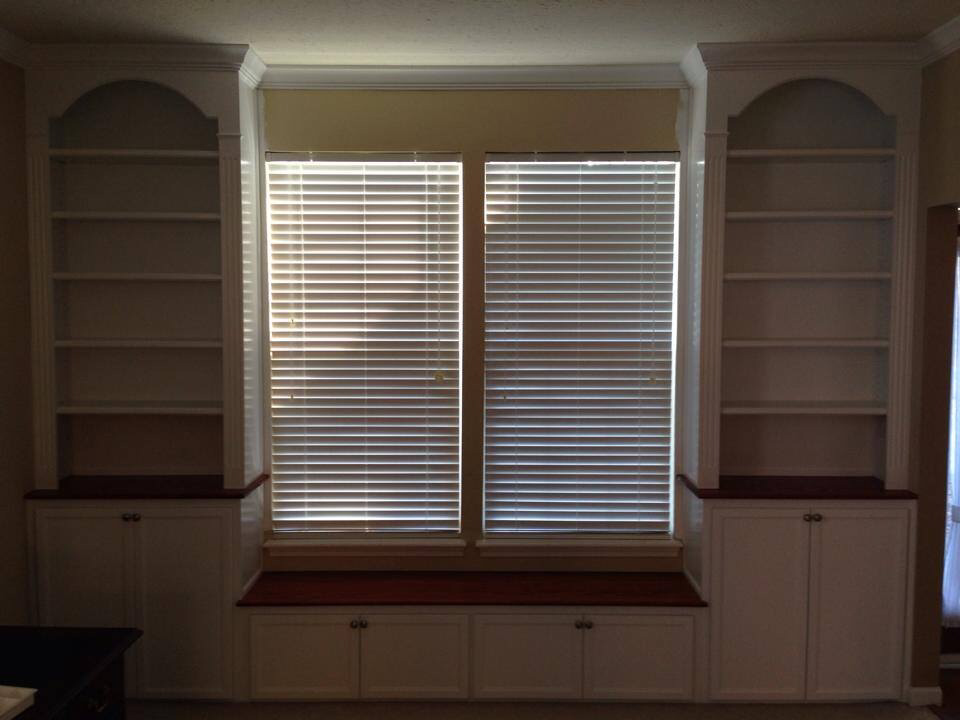Window seat built-in with base cabinets, bookcases with arched headers, fluted column style face frames, crown molding and stained bench top and cabinet tops.